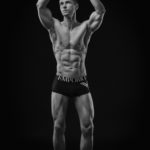 A fit man in underwear striking a classic bodybuilding pose