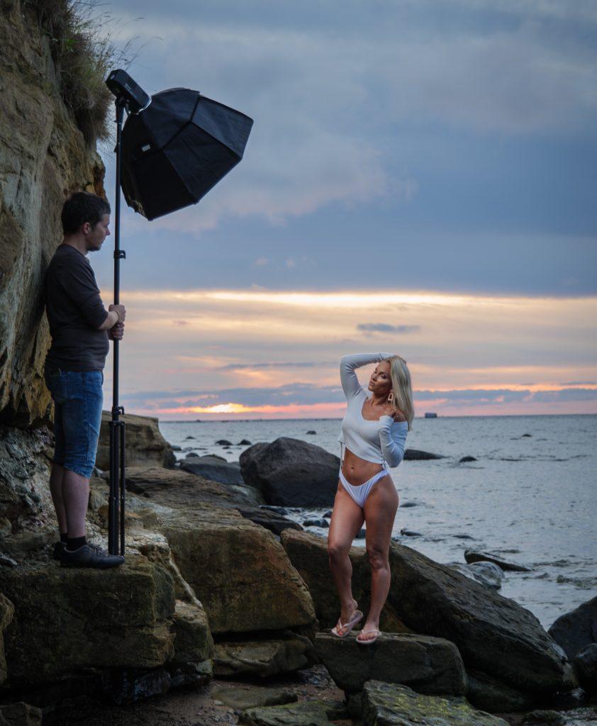Kõrvaltvaade, kuidas meie pildistamine käis - Tago on vasakul servas välku hoidmas ja sihtimas, Krista paremal mere taustal modelli rolli sisse elamas.